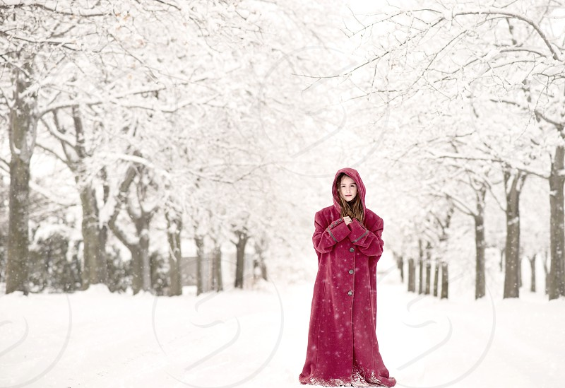 Pretty girl in red coat standing in the snow. photo