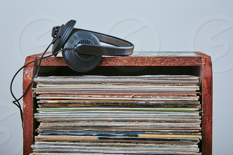 Stack of many black vinyl records and headphones put on the top of stack. Candid people real moments authentic situations photo