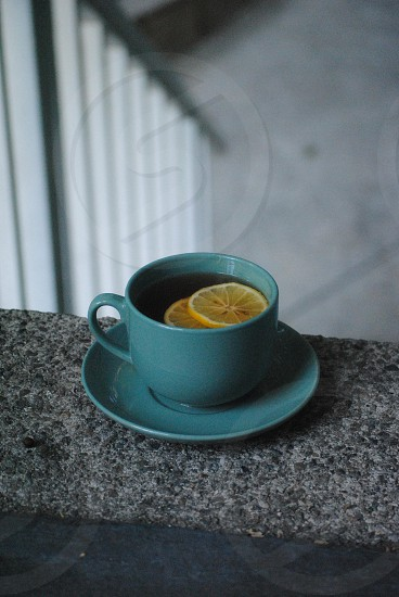 green ceramic cup and saucer with yellow sliced fruit photo