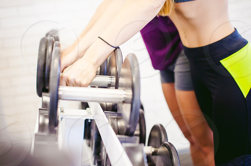 girl in a bright white gym. Two young athletic women near sports equipment are preparing for the traning with dumbbells holding up in their hands. Healthy way of life good spirits photo