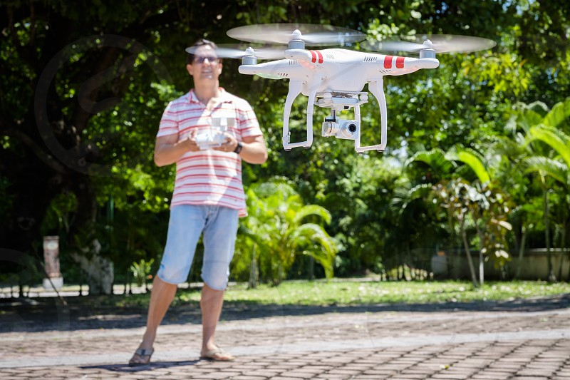 Caucasian man using remote control to operate a quadcopter drone hovering in air. photo