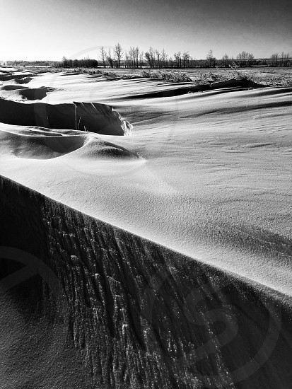Wind swept snows drifted across a ditch on a cold northern Alberta day. photo