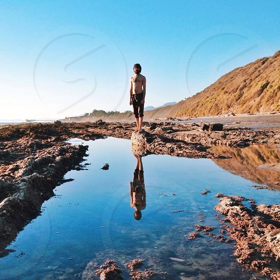 man in black capri pants standing on gray rock photo