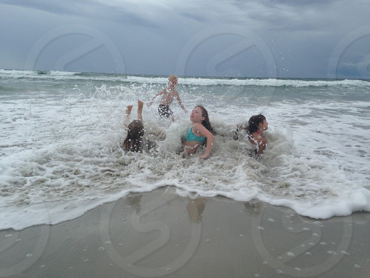 4 kids swimming in the sea photo