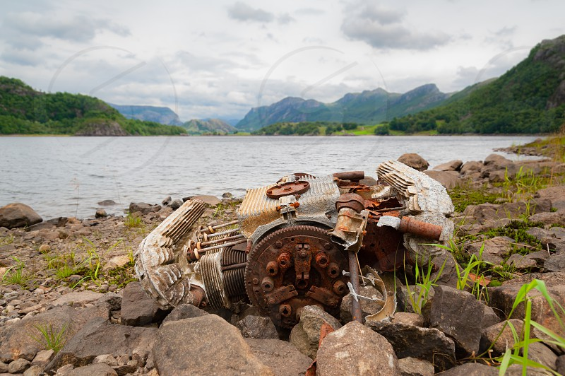 Old rusty car engine left abandoned on the banks of lake / water reservoir.  photo