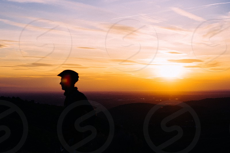 A mountain biker takes in the view at sunset in the foothills of Boise Idaho photo