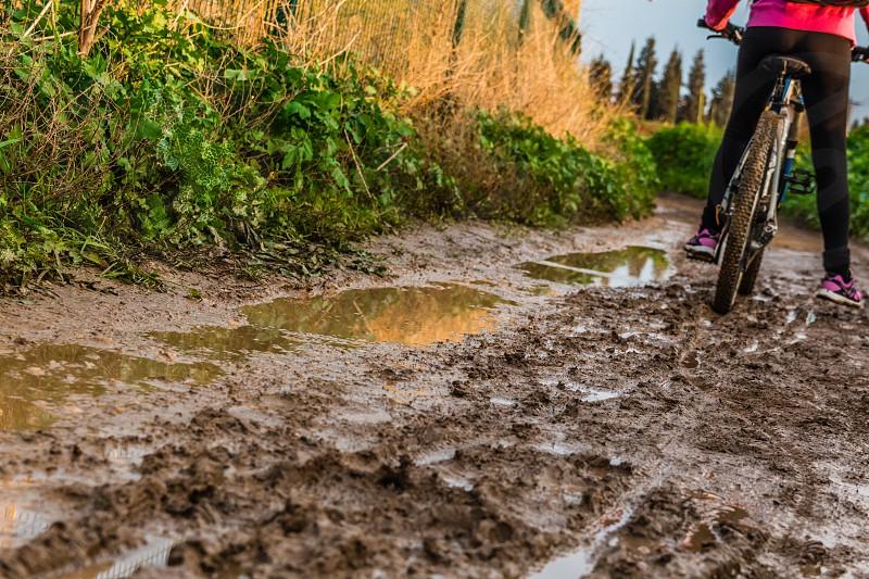 Bicycle ride through muddy dirt road. photo