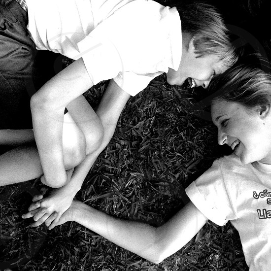 two people holding each other hand while lying on the grass photo