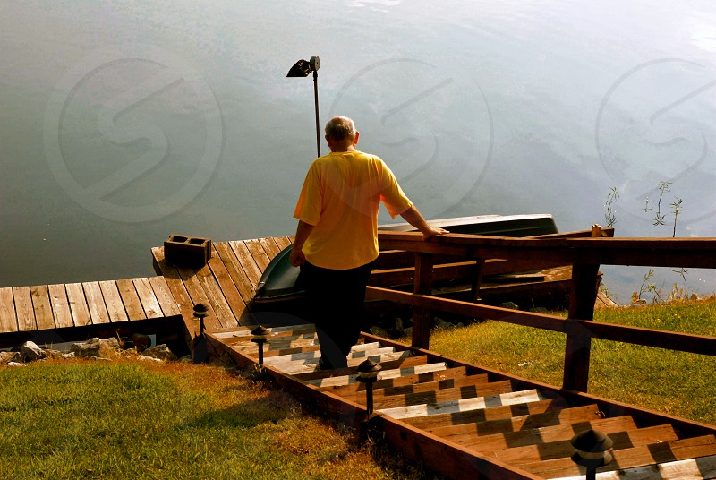 Old Man walks down the stair to the water photo