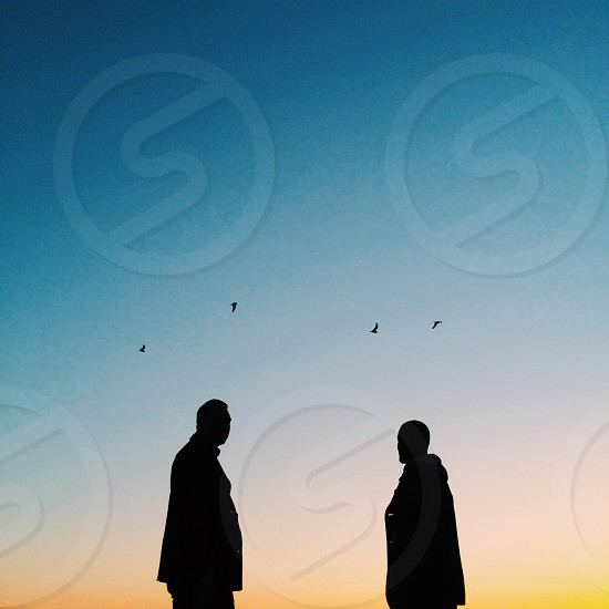 silhouette of two people standing below four birds flying in blue sky during sunset photo