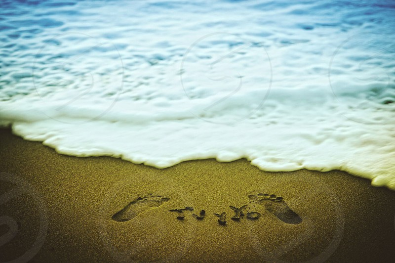 blue waters and brown sand with footprints photo