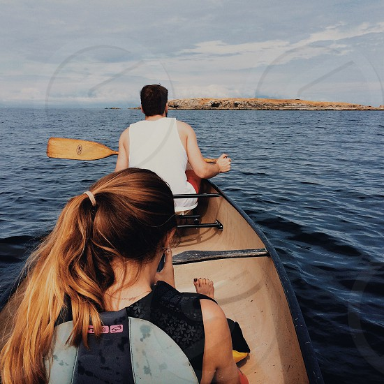 man and woman sitting in canoe photo
