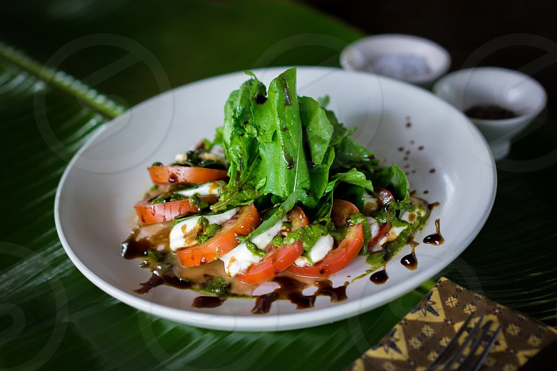 red slice tomato with white meat with green lettuce  on top with black sauce salad on white plate photo