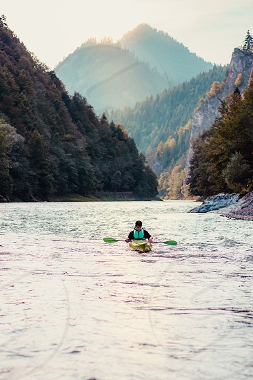 Young man kayaking on the Dunajec river sitting in a kayak and paddling down the river. Enjoying ride surrounded by hills and beautiful view of valley and mountains peaks. Spends vacation on wandering with backpacks in a mountains and forests photo
