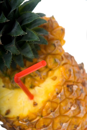 ripe pineapple cutted on top with red straw photo