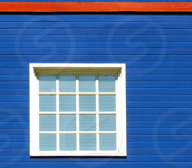 four by four paned window on a brightblue building photo