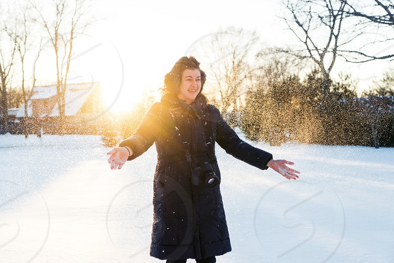 A young woman standing in snow smiles as she throws a handful of fresh powder into the air photo