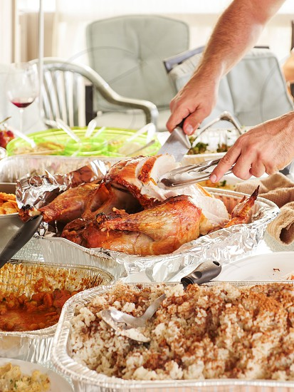 Hands Slicing with knife the holiday turkey on the holiday table close up  photo