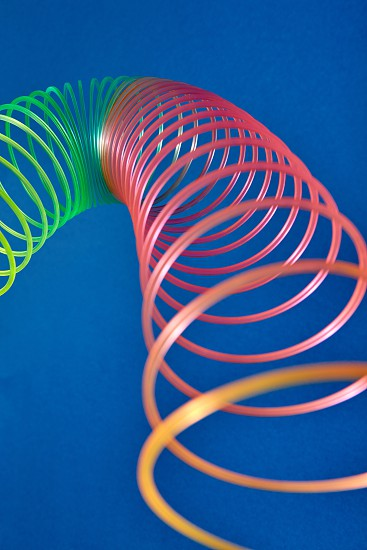Flexible stretching multicolored slinky toy close up view with blurred foreground place for text. photo