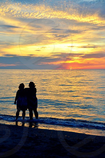 Two silhouettes on the beach at sunset photo