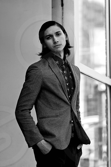 man in suit blazer and black casual pants in grayscale photography photo
