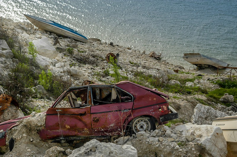 Vehicles unloved and abandoned. Not to mention rusted out and falling down into a lake. photo