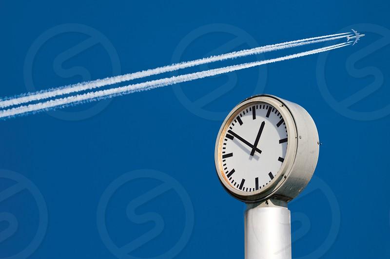airplane jet contrail clock time sky blue blue sky clear sky travel journey flight trip departure departure time airport airport detail photo