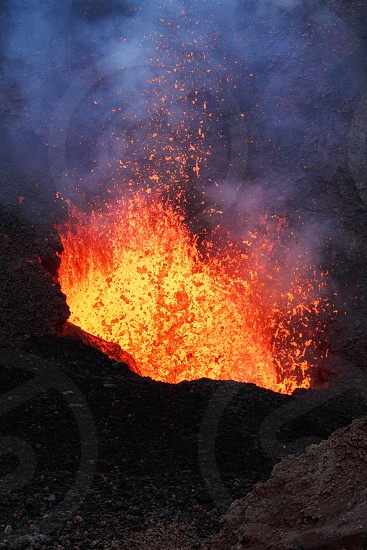 Volcanic landscape of Kamchatka Peninsula: night eruption active Tolbachik Volcano - lava lake lava flowing in crater of volcano. Russian Far East Kamchatka Region Klyuchevskaya Group of Volcanoes. photo