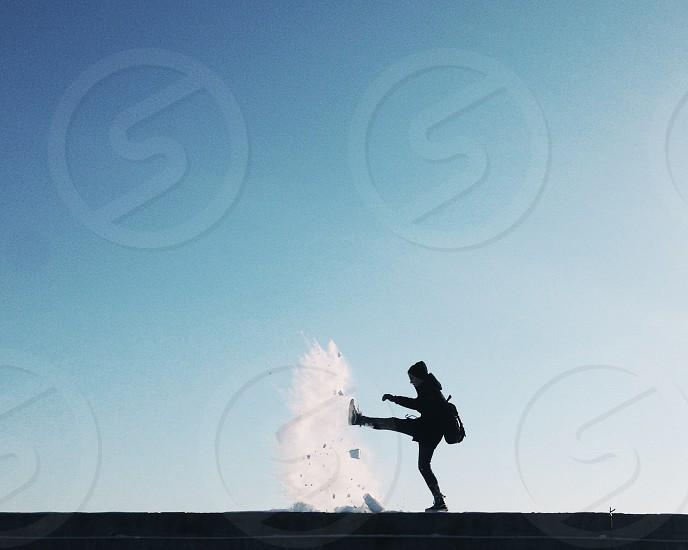 person in black jacket kick ice on floor photo