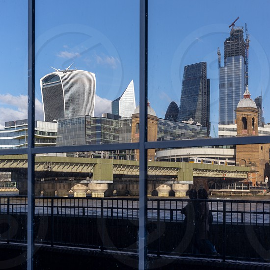 LONDON UK - MARCH 11 : City skyline reflected in a building on the south bank of the River Thames in London on March 11 2019. two unidentified people photo