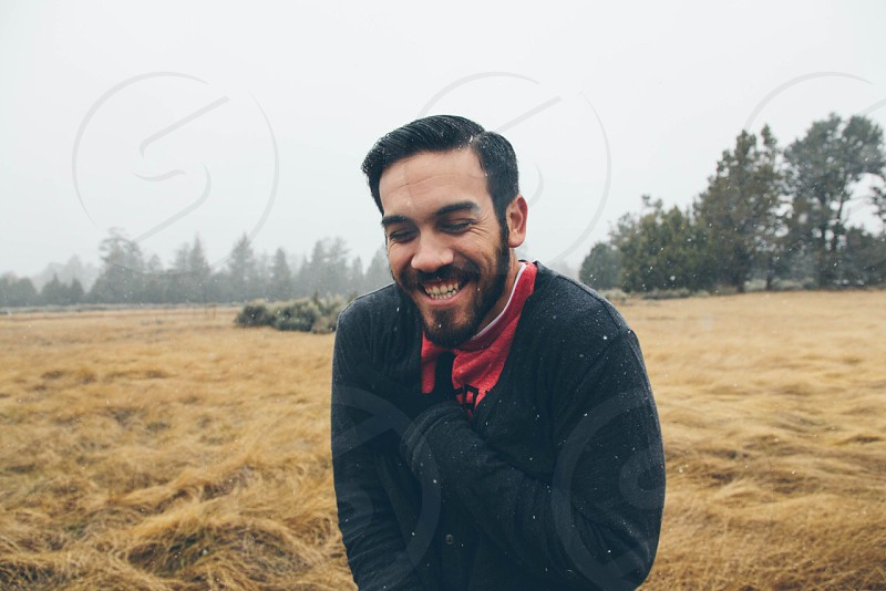man with black hair and beard smiling in open field wearing black sweater red shirt photo