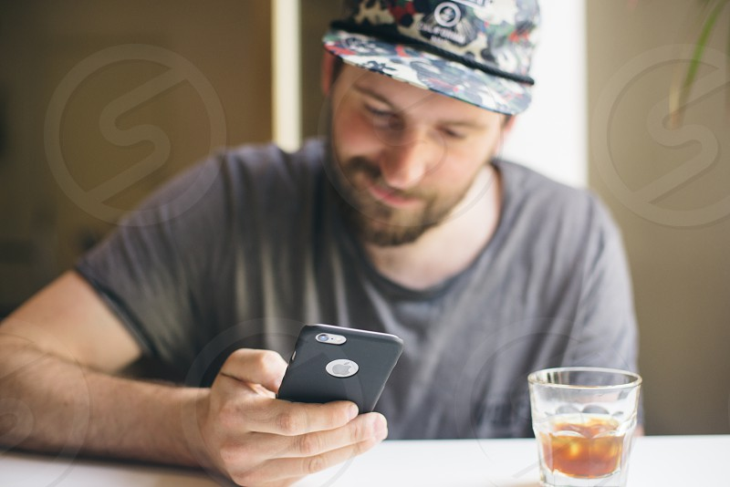 Guy with iPhone 6s in coffee shop photo