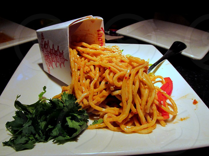 Noodles spilling out of chinese food container photo