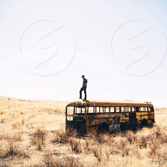 man on top of a yellow abandoned buss photo