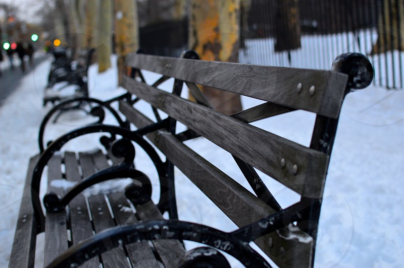 Bench up close with snow trees and walkway. photo