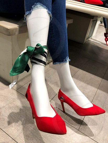 Women's legs jeans and red shoes. Green scarf on foot. From the series - women's legs are always attracted. photo