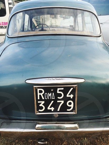 roma 54 3479 license plate on vintage teal car photo