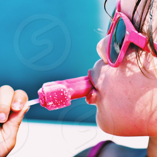 shallow focus photography of girl in pink wayfarer sunglasses eating pink Popsicle stick photo