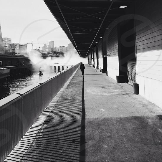 person walking along railing near waterfront building photo