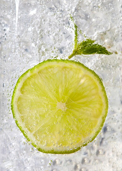 Fresh mint leaf and a slice of lime with bubbles in a glass with ice. Macro photo of refreshing drink photo