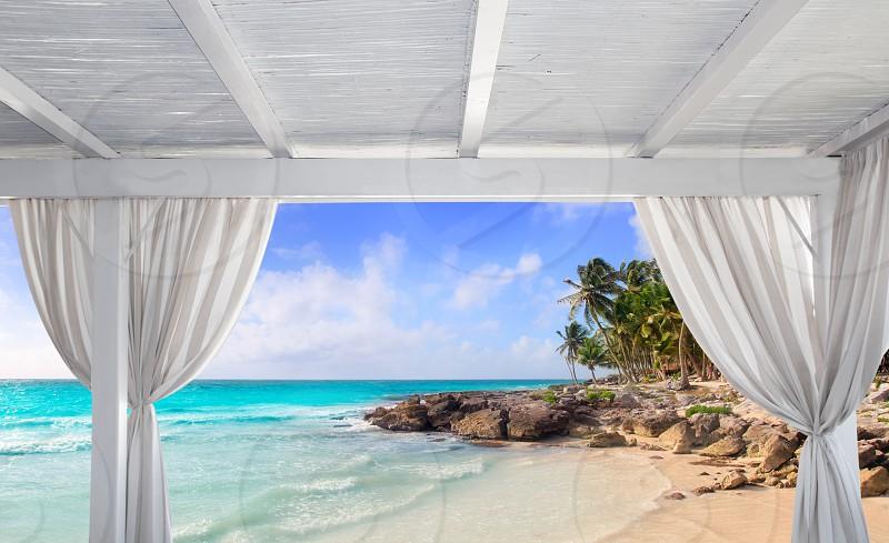 Gazebo white in tropical Caribbean beach with palm trees photo