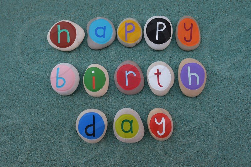 Happy Birthday text composed with round painted stone letters over green sand photo