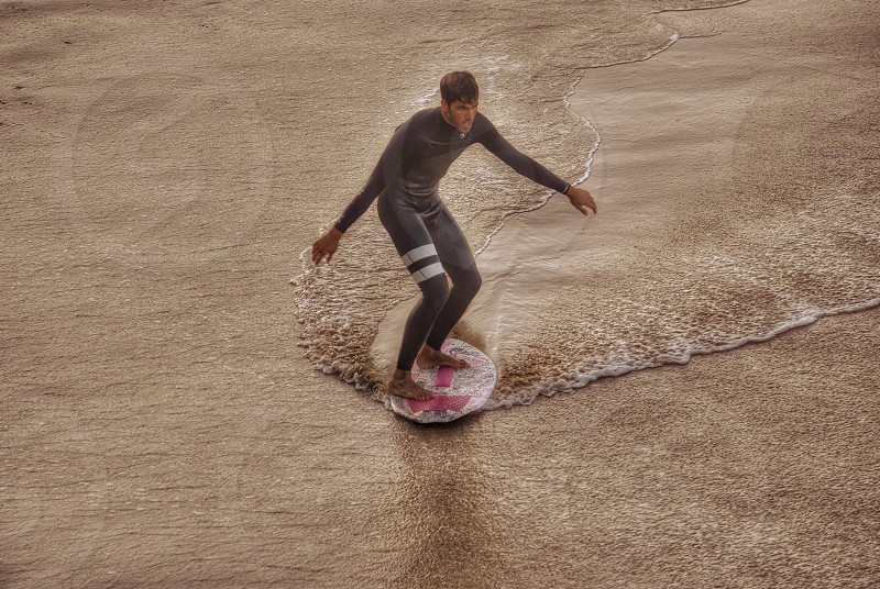 man in a scuba suit surfing on water photo