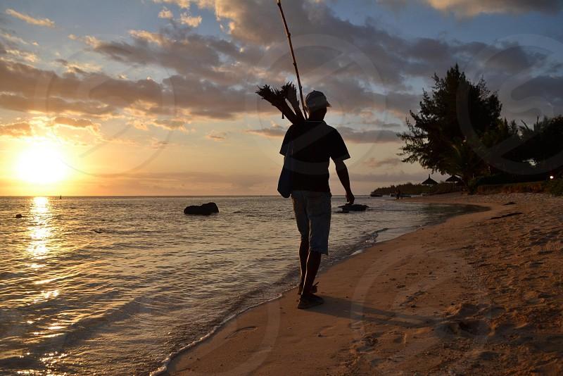 Beach. Local fisherman. Sunset. Mauritius.  photo