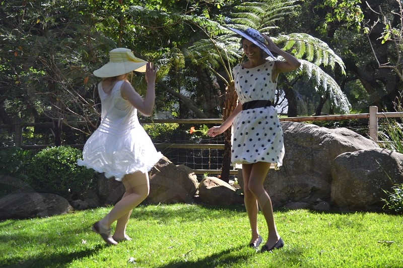 2 woman in white dresses standing on lawn photo