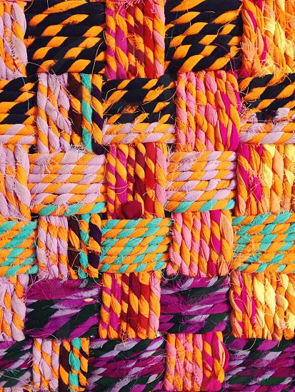 yellow white pink black and red woven textile photo