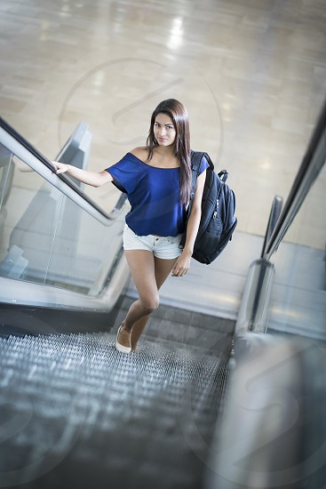 Young beautiful woman with backpack going up on an escalator photo