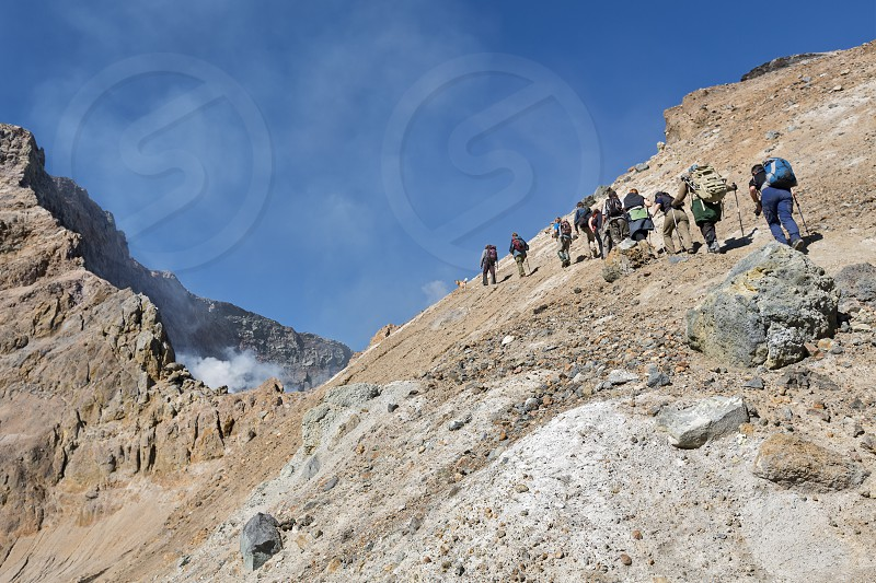 KAMCHATKA RUSSIA - SEPTEMBER 11 2013: Group of tourists climbing on the steep slope to the active crater Mutnovsky Volcano. Kamchatka Peninsula Russia Far East. photo