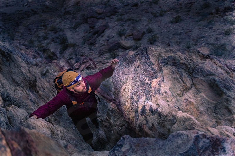 A rock climber ascends a mountain in the dark by headlamp. photo