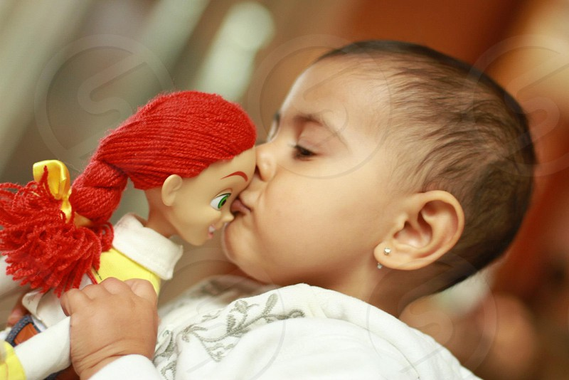 baby girl kissing a doll photo